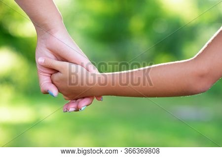 Mother leads her kid in summer forest nature outdoor. Trust, family, protection and help concept. Female and child's hands closeup against the background of summer greenery. Parent walks with daughter
