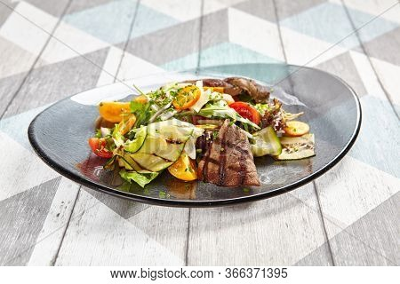 Salad with veal and kumquat. Restaurant meal served on transparent plate. Beef steak with raw vegetables mix side view. Grilled meat with garnish close-up. Delicious main course on table