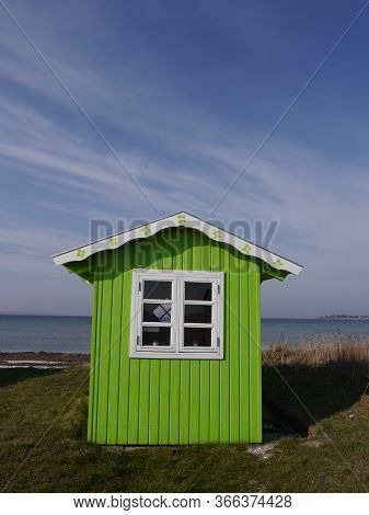 A Cute Lime-green Beach Hut With Background Of Blue Sea And Sky.