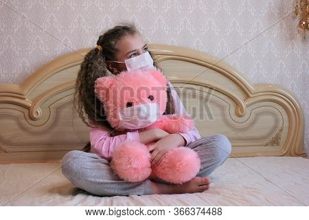 A Girl In A Face Mask Sits At Home On A Bed And Hugs A Pink Teddy Bear In A Face Mask.
