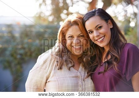 Portrait Of Senior Hispanic Mother With Adult Daughter In Garden At Home