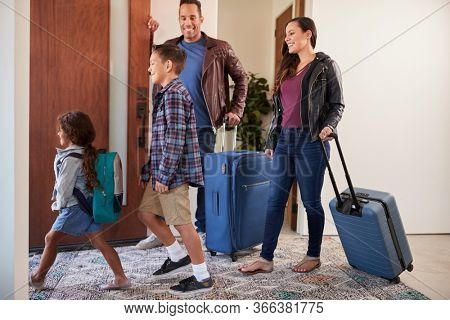 Family With Luggage Opening Door And Leaving Home For Vacation