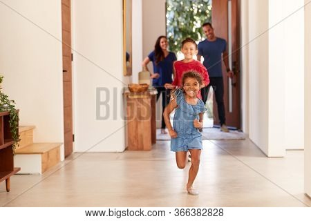 Excited Family Returning Home After Trip Out With Children Running Through Front Door