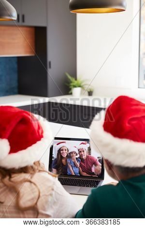 Multi-Generation Hispanic Family Wearing Santa Hats With Laptop Having Video Chat At Christmas