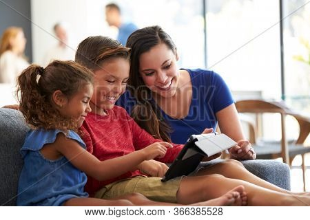 Mother Playing Video Games With Children On Digital Tablet During Family Gathering At Home