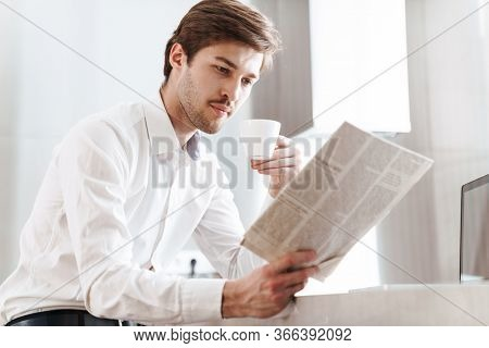Photo of thinking brunette businessman wearing shirt drinking coffee and reading newspaper at modern kitchen