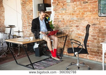 Doubt. Young Man Without Pants But In Jacket Working On A Computer, Laptop. Remote Office During Cor