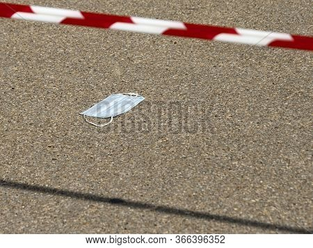 Used Disposable Medical Face Mask Lying On The Road With Red And White Striped Barricade Tape