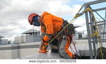 Professional Industrial Climber In An Orange Suit Checks And Installs The Seat And Checks The Insura