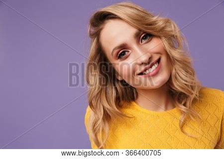 Image of nice cheerful woman smiling and looking at camera isolated over purple background