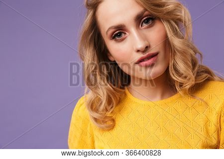 Image of nice serious woman posing and looking at camera isolated over purple background