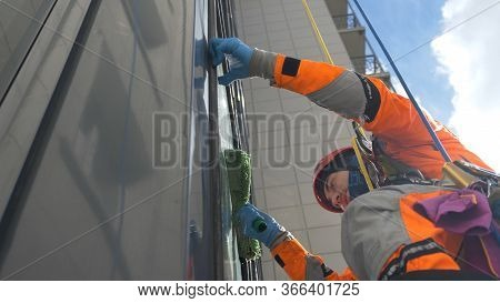 Professional Industrial Climber Man In A Helmet And Gloves Washes The Windows With A Fur Coat At Hig