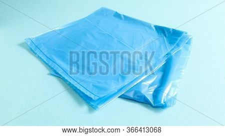 One Torn Plastic Garbage Bag In Blue On A Blue Background. A Bag That Is Designed To Accommodate Gar