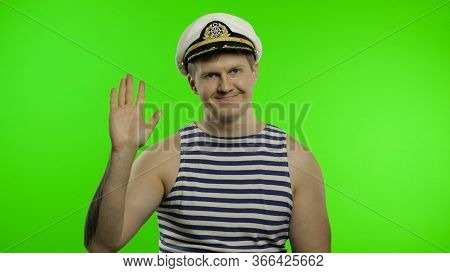 Young Muscular Sailor Man Waving Hand. Seaman Guy Smiling In Sailors Vest. Striped Navy White And Bl