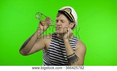 Young Drunk Muscular Sailor Man Drinks Vodka From Bottle. Seaman Guy Smiling In Sailors Vest. Stripe