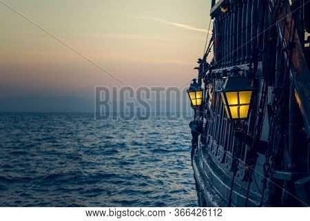 Old Wooden Vintage Pirate Ship On Sea Water Surface In Sunset Evening Romantic Time With Yellow Ligh