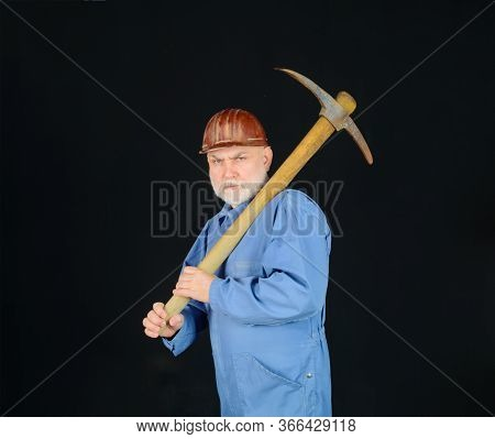 Man Contractor Holds Pickaxe. Serious Construction Worker With Pickaxe. Workman With Pick Axe. Male
