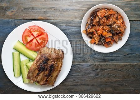 Grilled Pork Ribs With Sliced Cucumbers And Tomatoes On A White Plate. Pork Ribs On Blue Wooden Back