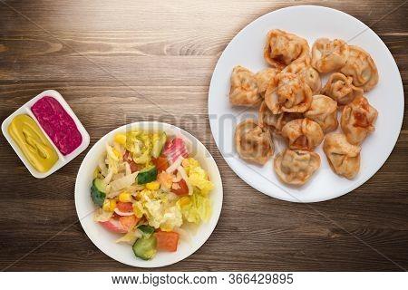 Dumplings On A White Plate On Brown Wooden Background. Dumplings In Tomato Sauce With Salad. Dumplin