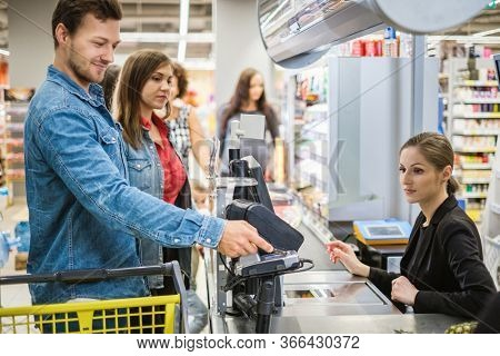 Man paying with contactless card in a grocery store