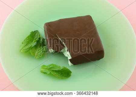 Mint Chocolate Chip Ice Cream Bar Covered In Milk Chocolate On Green Plate With Fresh Mint Leaves On