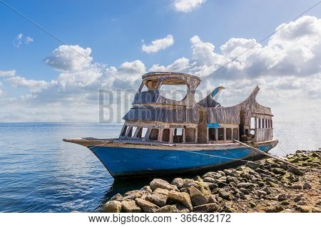 Shabby Aged Boat Floating In Sea Water Near Rocky Coast Against Cloudy Sky