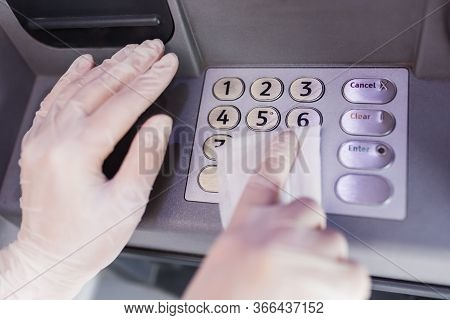 Close Up Of Hands Wearing Protective Medical Gloves Cleaning Numeric Atm Keyboard With Wet Wipe. Pub