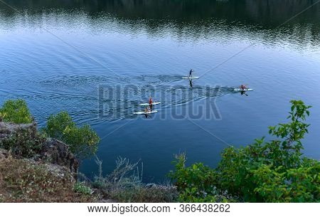 A Group Of People Are Swimming Standing With Oars On A Padboard On The River. Rocky Shore