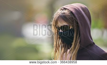 Portrait Of A Girl With Dreadlocks In A Protective Medical Mask. Girl In Glasses And A Hood.