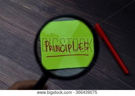 Principles Write On Sticky Note With Magnifying Glass Isolated On Wooden Table.
