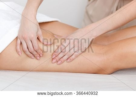 Young Woman Massage Therapist Makes Hands Anti-cellulite Procedures On The Skin Of The Hips Of A Gir
