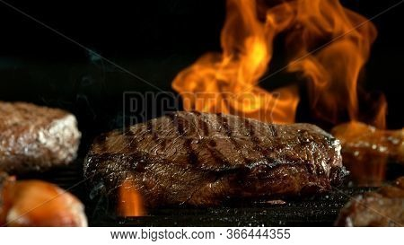 Raw beef burger steak on grill. Cutlet meat placed on grill grid with fire. Black background.
