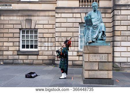 EDINBURGH,UK - AUGUST 14,2019 : Bagpipe player in traditional scottish kilts next to the David Hume statue in Edinburgh