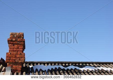 Brick Chimney. Snow On The Roof. Heating Season.