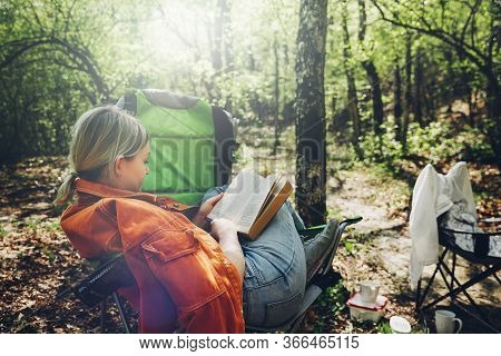 Finding Solitude In Wilderness Concept. Young Woman Resting In Forest, Sitting In Camp Chair And Rea