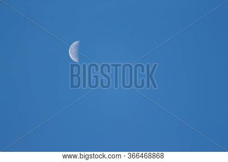 Moon Lunar / Luna On The Blue Sky. Half Lunar Moon In A Clear Daylight Sky. Earth Moon Lunar On Day