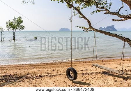 Covid-19 Lockdown. Empty Wooden Swing & Tyre Hang From Tree On Deserted Beach On Ko Yao Noi Island I