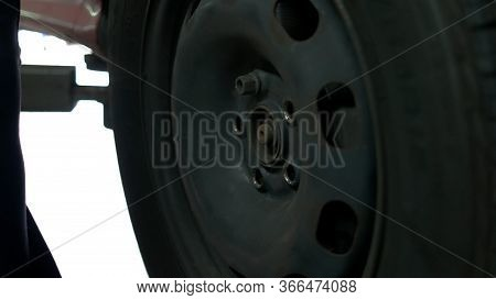 Close Up Man Unscrewing Car Wheel. Removing Nuts Using Electrical Screwdriver.