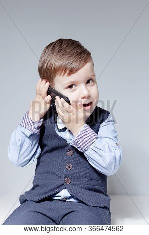 A Boy In A Shirt, Bow Tie, Vest And Trousers On A White Background Is Talking On The Phone. Stylish