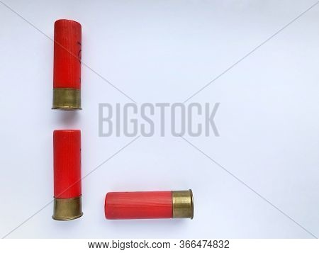 Several Hunting Cartridges And Scattered Pellets Of Cartridges Isolated On A White Background.