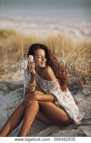 Summer Travel Vacation Relaxation Concept. An Attractive Brunette Woman With Shell Sitting On A Sand