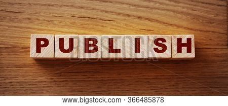Publish Written On A Wooden Cube On A Wood Desk. Publishing News Concept