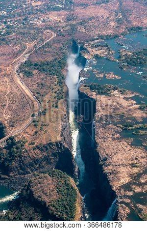 Spectacular Aerial Of Victoria Falls Waterfall And Bridge Across The Zambezi, Zimbabwe, Africa In Po