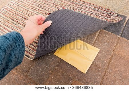 Person Lifting Doormat To Reveal Small Package Left Underneath
