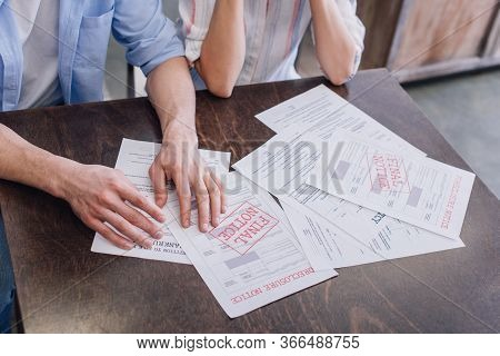 Cropped View Of Man And Woman With Documents With Foreclosure And Final Notice Lettering At Table
