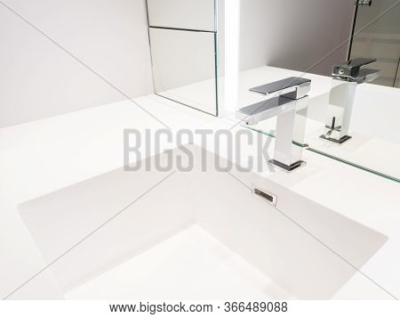 Faucet And White Washbasin In The Bathroom.