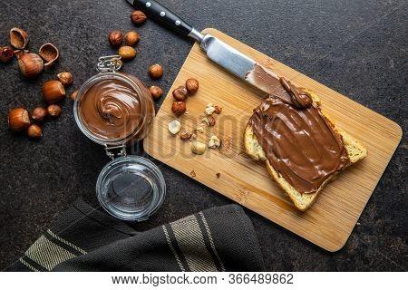 Toast bread with hazelnut spread. Sweet chocolate cream on cutting board. Top view.