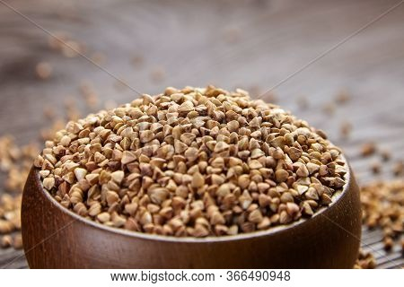 Buckwheat Groats (hulled Seeds) In Wooden Bowl, Selective Focus. Buckwheat Whole Grains On Brown Tab