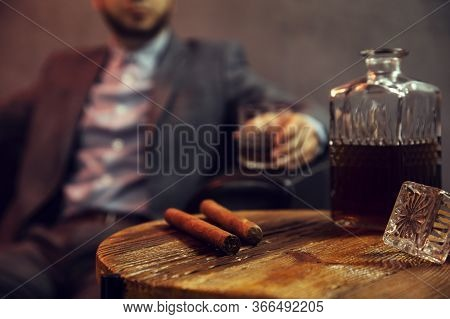 Two Cigars And A Carafe Of Whisky On Wooden Table And An Elegant Man With The Glass Of Whisky In The