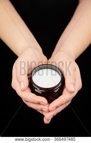 Shea Butter In Jar, Cosmetic Product For Moisturizing Skin. Female Hand Holds Container With White A